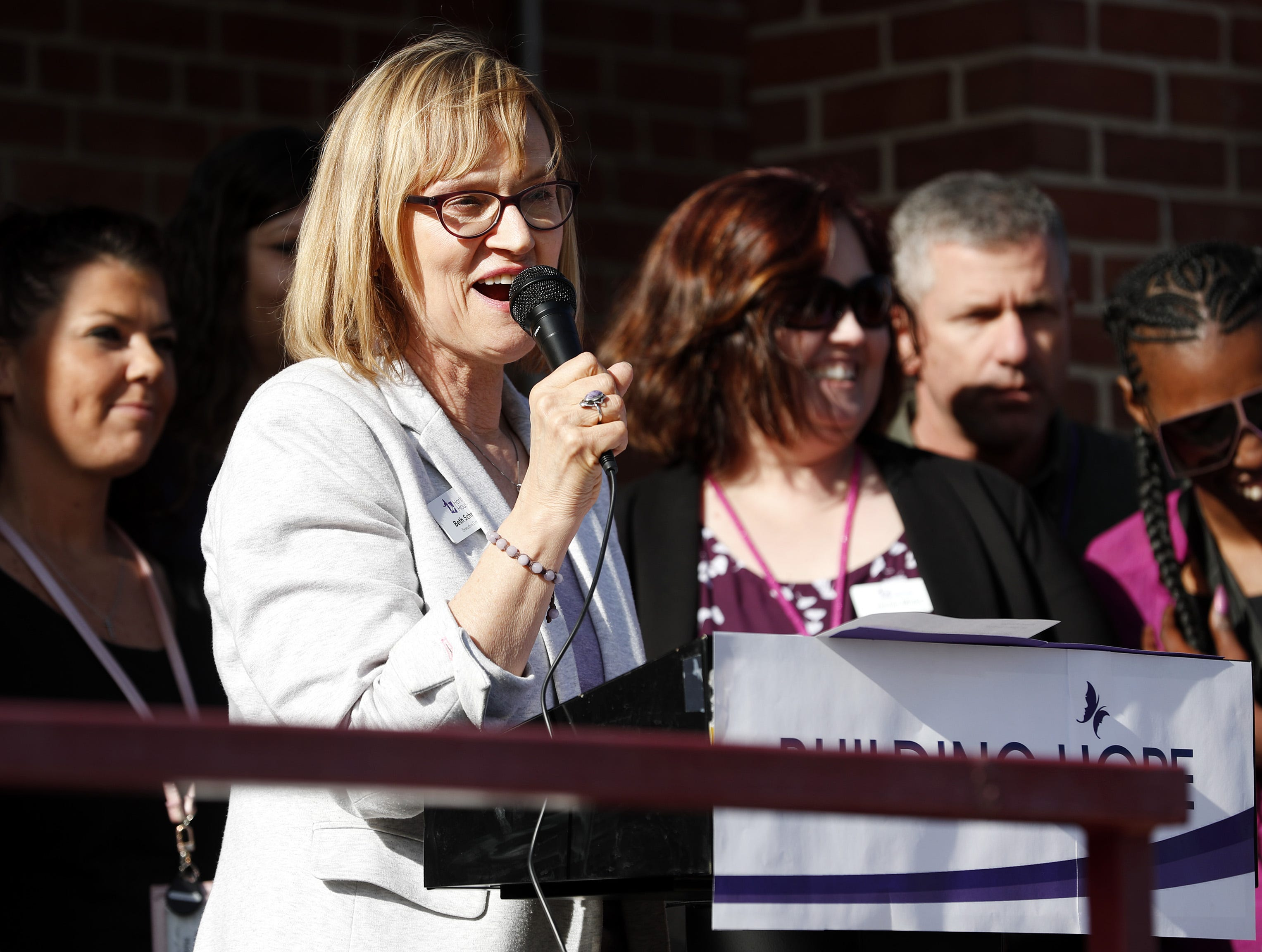 Beth Schnorr, executive director of Harbor House Domestic Abuse Programs, speaks Tuesday to a crowd gathered at the ribbon cutting and open house for Harbor House's updated facility.