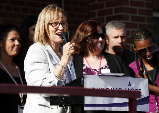 Beth Schnorr, executive director of Harbor House Domestic Abuse Programs, speaks to a crowd in May at the ribbon-cutting ceremony for the agency's expanded facility in Appleton.