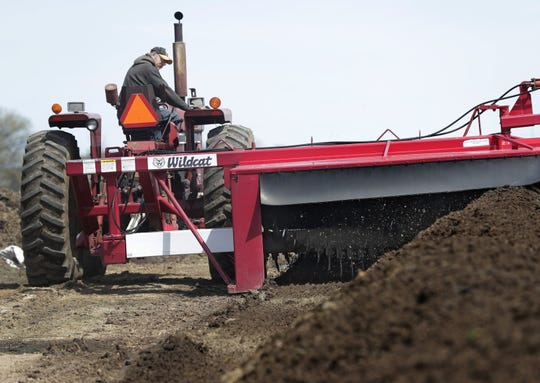 Steve Petersen turns compost to aerate so bacteria can break down cow manure. His brother Mark said he is open to listening to the details of the Green New Deal in how it would affect agriculture.