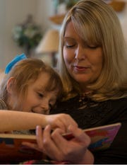 Amie Cottrell reads a book with her daughter Katelyn, 4.