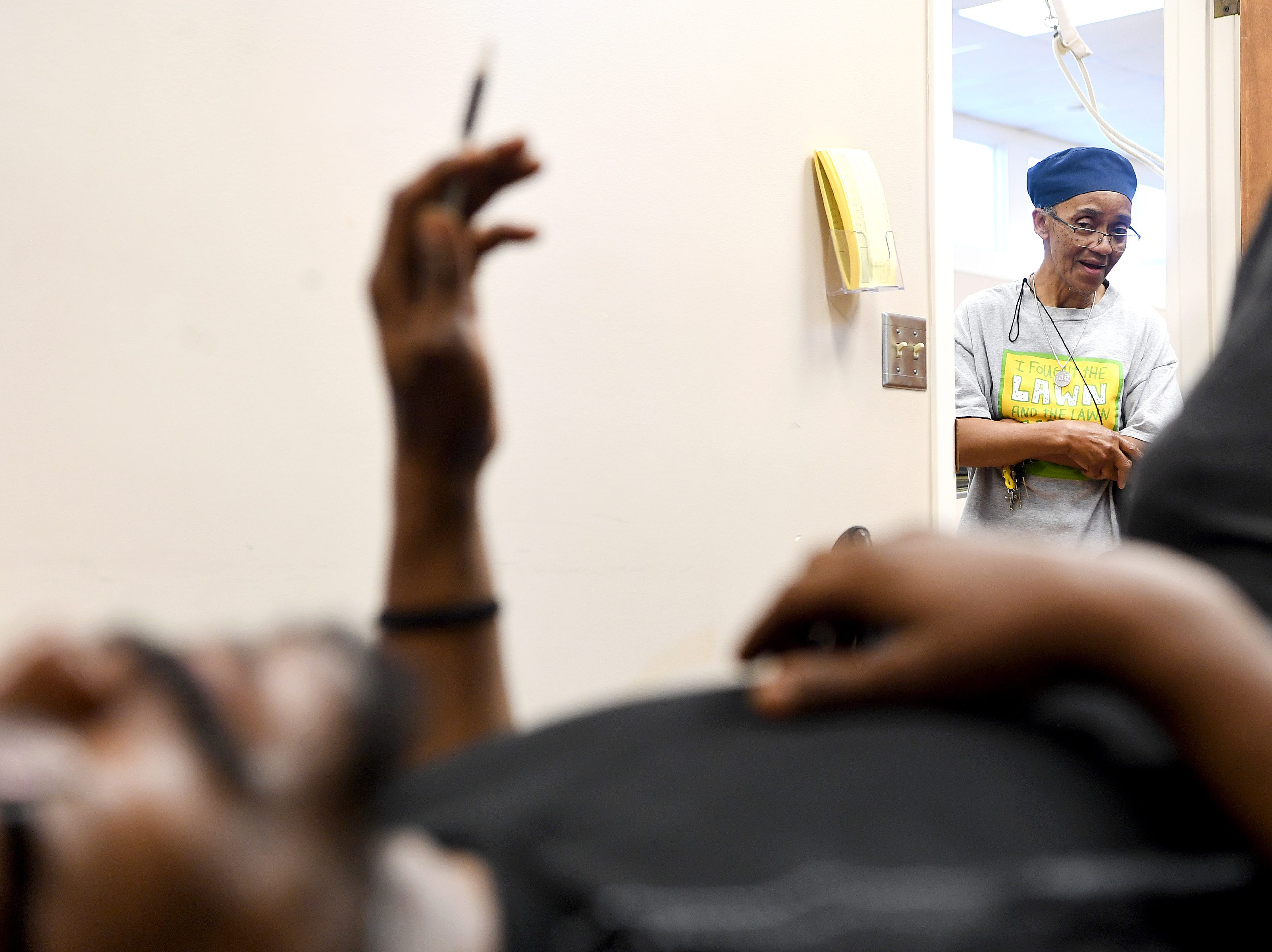 Hanan Shabazz peeks through the doorway as Octavius Boozier stretches during physical therapy at CarePartners  on May 8, 2019. Shabazz has been a surrogate grandmother for Boozier and was by his side during his extensive stay in the hospital.