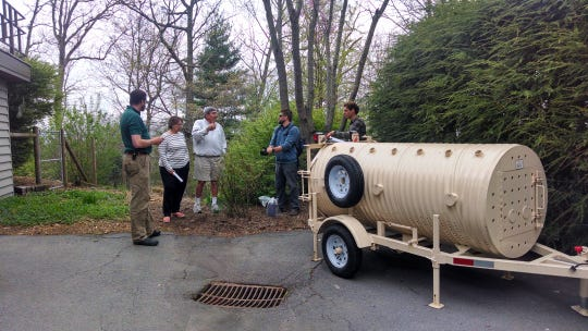 Researchers with the Asheville Urban/Suburban Black Bear Study talk to homeowners about how a bear trap works.
