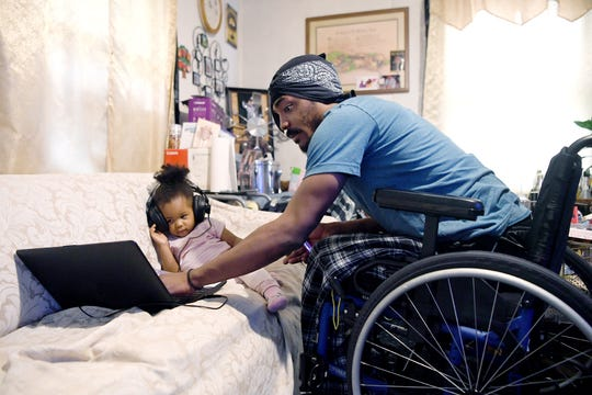 Octavius Boozier helps his daughter, Kallie, 2, with a video on his laptop as he cares for her on April 26, 2019.