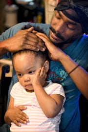 Octavius Boozier tries to pull back his daughter, Kallie's, 2, hair as he cares for her on April 26, 2019.