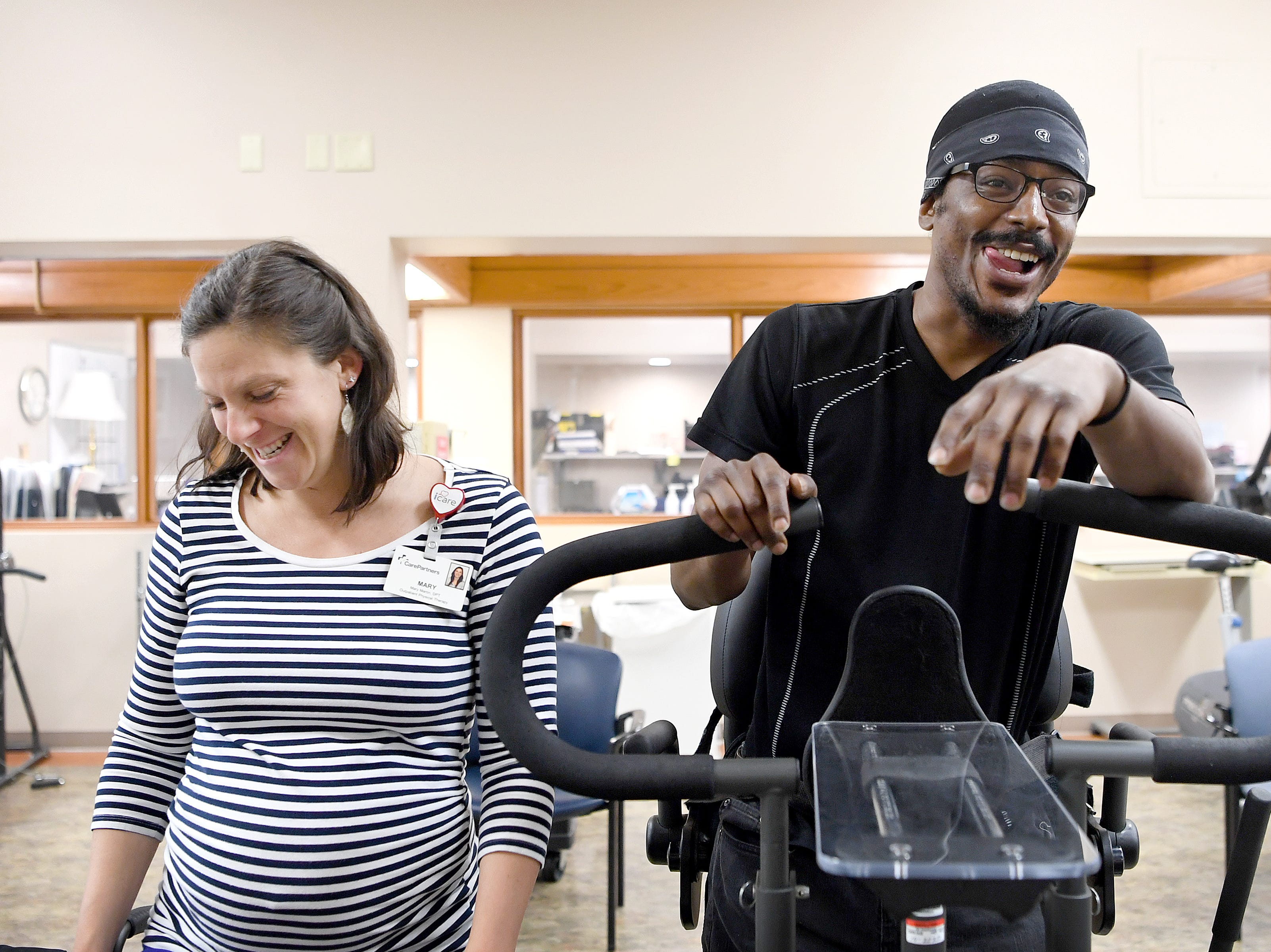 Physical therapist Mary Martin laughs with Octavius Boozier as he uses a machine to help him strand during an appointment at CarePartners on May 8, 2019. Boozier has limited use of his feet after being shot in the back in November 2017 but hopes to one day be able to walk again.