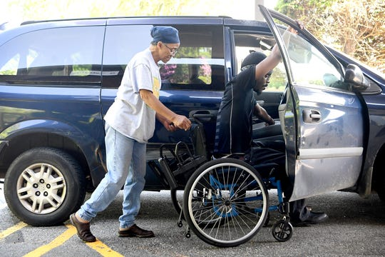 Hanan Shabazz helps Octavius Boozier into his wheelchair from the front seat of her van at CarePartners for a physical therapy appointment on May 8, 2019. Shabazz currently transports Boozier to all of his appointments, school and anywhere else he needs to go.