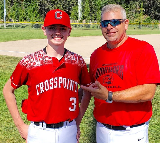 Crosspoint pitcher Gage Broderson (left) smiles with head coach Derrin Doty after pitching a no-hitter in Tuesday's district playoff game against Orcas Island.
