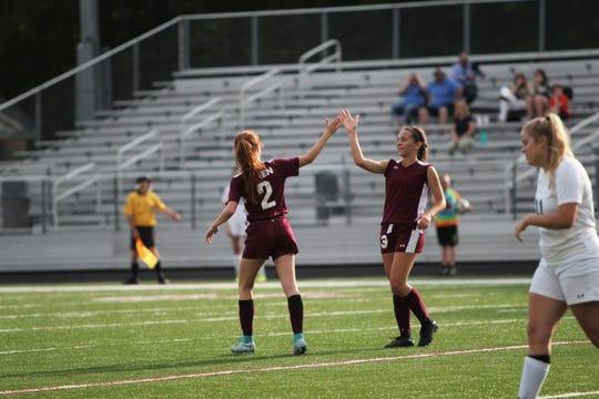 Owen senior Carly Campbell (2) congratulates junior Camryn Bolick for scoring a goal in an 8-2 win over Smoky Mountain in the opening round of the playoffs.