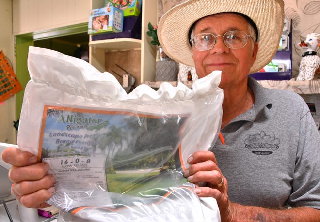 Dave Grover, owner and founder of Sun Harbour Nursery in Indian Harbour Beach, shows a brand of fertilizer he recommends. Grover supports the just-approved  county ordinance amendment requiring retailers to post signs letting customers know about restrictions on fertilizer use.