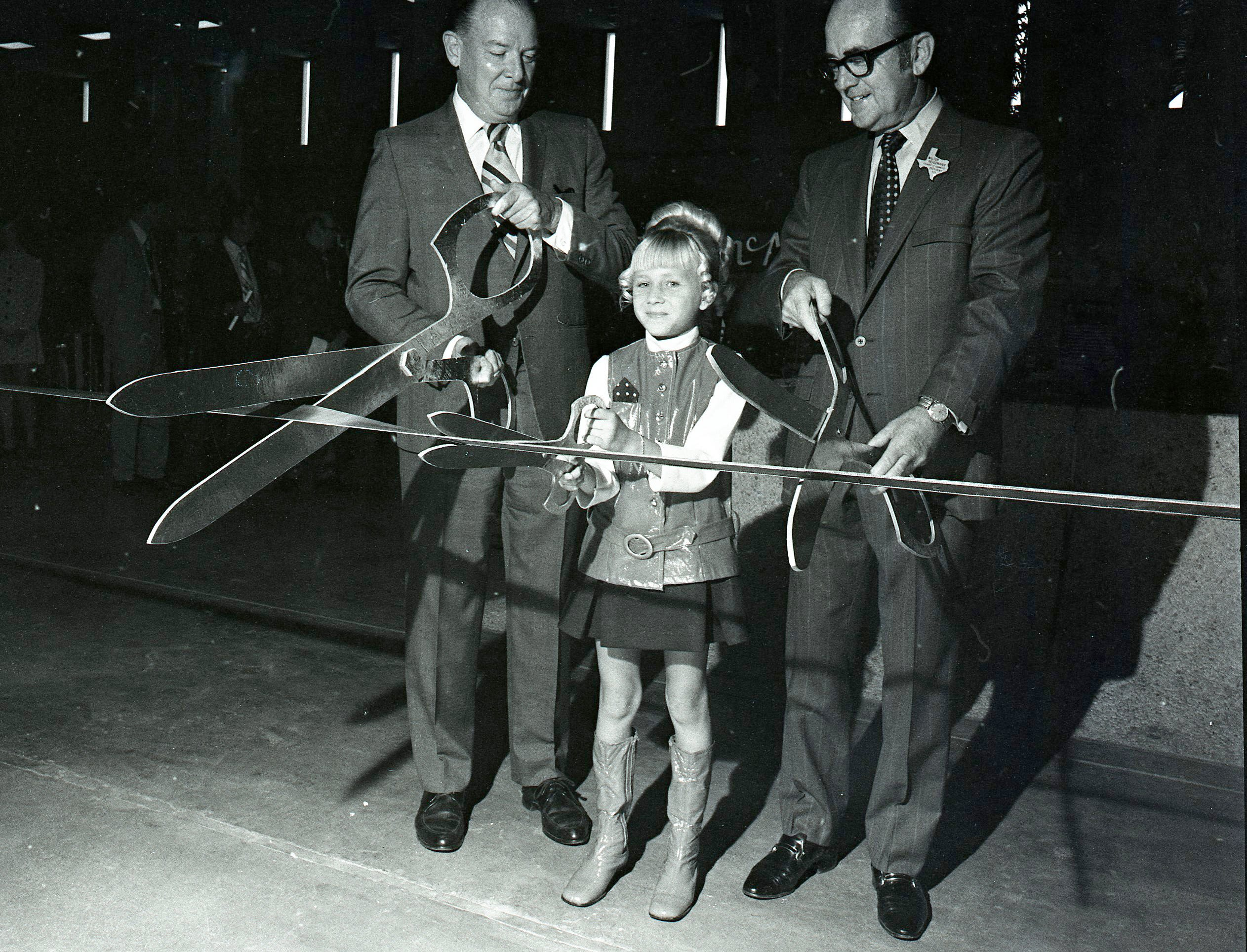 Margo Deckert, 9, grandaughter of mall owner Roy Smith, uses a smaller set of shears as at the ribboncutting for Padre Staples Mall in Corpus Christi on July 30, 1970. She was joined by William H. Keys (left), president of the South Texas Chamber of Commerce, and Walter J. Reasonover (right), president of the Corpus Christi Chamber of Commerce.
