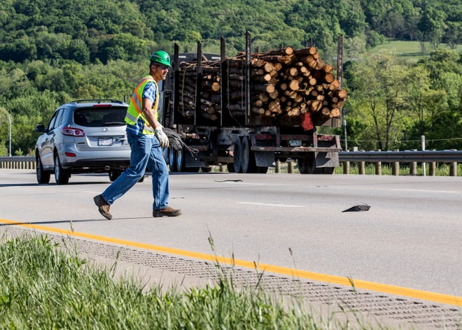 Ohio Department of Transportation manager Matt Hayes runs onto the highway to collect tire remnants at the split of U.S. 23 and U.S. 35 near East Main Street.