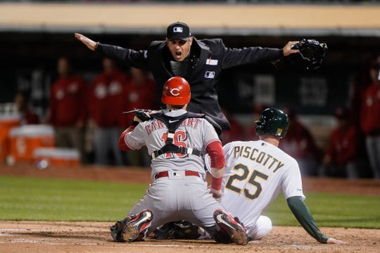 May 7, 2019; Oakland, CA, USA; Umpire Mark Ripperger (90) calls Oakland Athletics right fielder Stephen Piscotty (25) safe as Cincinnati Reds catcher Tucker Barnhart (16) looks for the call during the second inning at Oakland Coliseum. Mandatory Credit: Stan Szeto-USA TODAY Sports