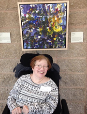 Cheryl Chapin pictured in front of her painting at last year's exhibit at Rutgers.