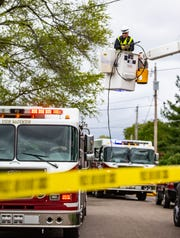 A MidAmerican worker removes a power line that fell on a firetruck as firefighters respond a house fire at 1515 4th St. in Des Moines Wednesday, May 8, 2019.
