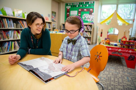 Fionnuala Hutchins, head of youth services at the Grimes Public Library, reads a book with 8-year-old Charlie Borcherding at the library. Grimes is among nine metro libraries partnering to offer new sensory-friendly browsing hours on a rotating basis.