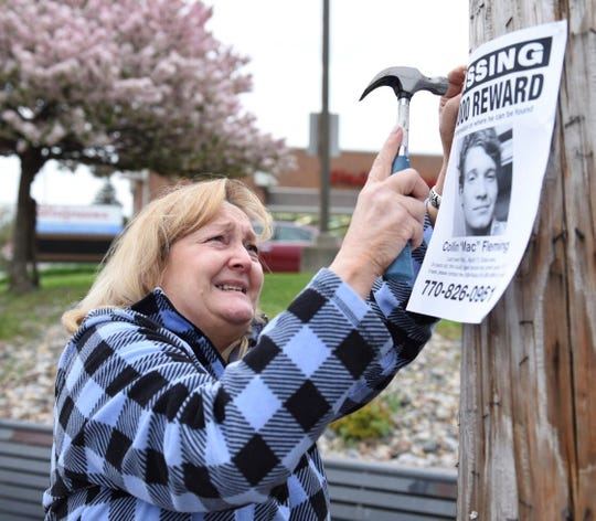 "Ingrid Fleming, 58, nails up a missing person sign featuring her 24-year-old son, Collin ""Mac"" Fleming, on Tuesday, May 7, 2019, in Des Moines' Drake neighborhood."