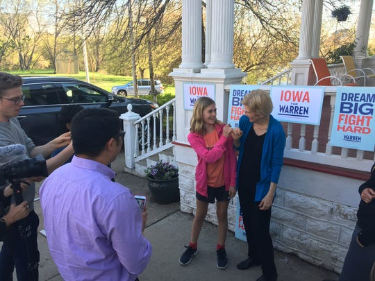 Sen. Elizabeth Warren makes a pinky promise with 10-year-old Robyn Kelsey after a house party in Iowa Falls.