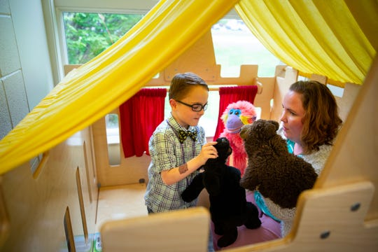 Charlie Borcherding, 8, and his mother Erika play with puppets at the Grimes Public Library Tuesday, May 7, 2019.