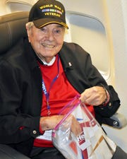 "This Saturday, May 4, 2019, photo from Honor Flight San Diego shows Frank Manchel, a 95-year-old former soldier, aboard an airliner taking him to Washington, D.C., on what's known as an Honor Flight for elderly veterans. Manchel collapsed about an hour before the chartered American Airlines jet was due to land on his return to his San Diego, Sunday. Two physicians, including his own son, Dr. Bruce Manchel, were unable to revive him. Passengers sang ""God Bless America"" as the plane descended, and saluted his body as they passed by on leaving the plane. (Teri Simas/Honor Flight San Diego via AP)"