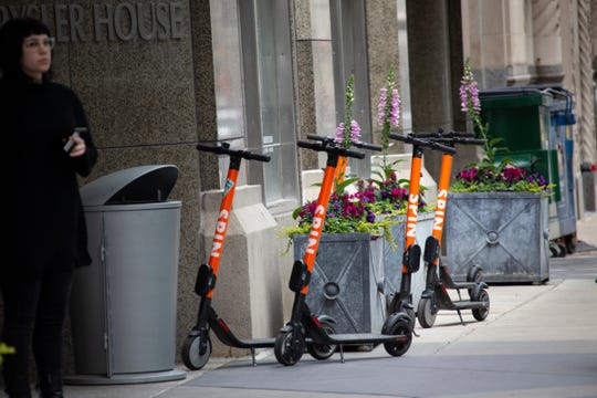 A group of Spin scooters sit outside of Chrysler House on Griswold Street in Detroit Wednesday, May 8, 2019.