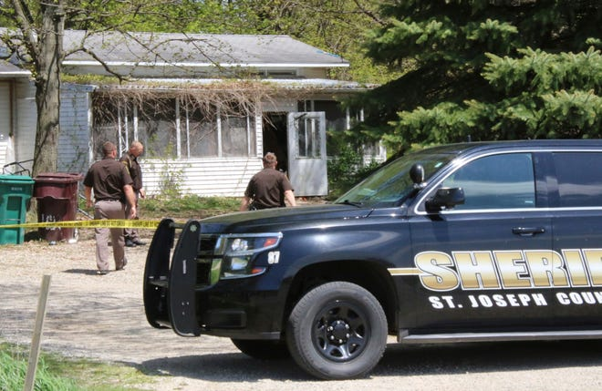 In this Monday, May 6, 2019, photo, St. Joseph County Sheriff deputies stand outside the site where a woman was fatally shot in Fawn River Township, Mich. Authorities say a 9-year-old is suspected in the shooting of a woman in her southern Michigan home.