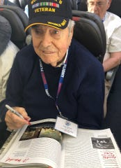 Frank Manchel signs a book about an hour before he collapsed May 5, 2019, on a flight home to San Diego.