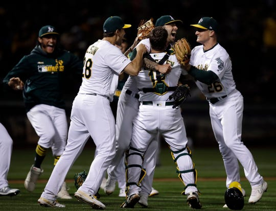 The Oakland Athletics' Mike Fiers, center, celebrates with Matt Olson (28), Chad Pinder (18) and Matt Chapman (26) after pitching a no-hitter against the Cincinnati Reds.