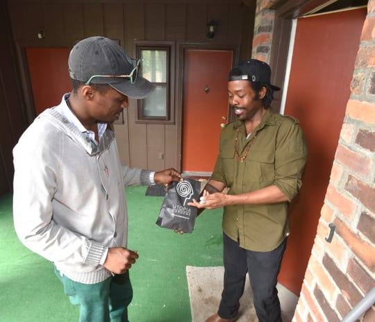 Utopia Gardens General Manager Donnell Cravens, left, makes a delivery to medical-marijuana patient Rashon Massey at his home on Van Dyke near Agnes in Detroit.