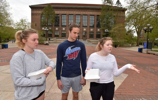 Grace Fanning, left, of New Jersey, Jason Knopf, of the Chicago area and Meg Wynne, of Indianapolis, talk about school debt on the Diag on the main campus of the University of Michigan in Ann Arbor.