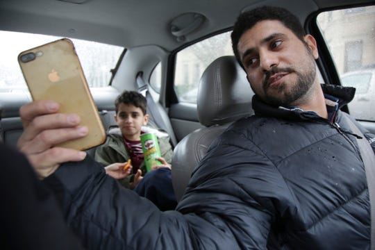Sadek Ahmed and his son Adel, 9, video chat with Sadek's wife before driving to a doctor's appointment in the Brooklyn borough of New York.
