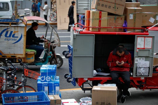 A private delivery company's courier sits on his delivery cart sorting boxes of goods for his customers outside an office building at the Central Business District in Beijing, Wednesday, May 8, 2019.