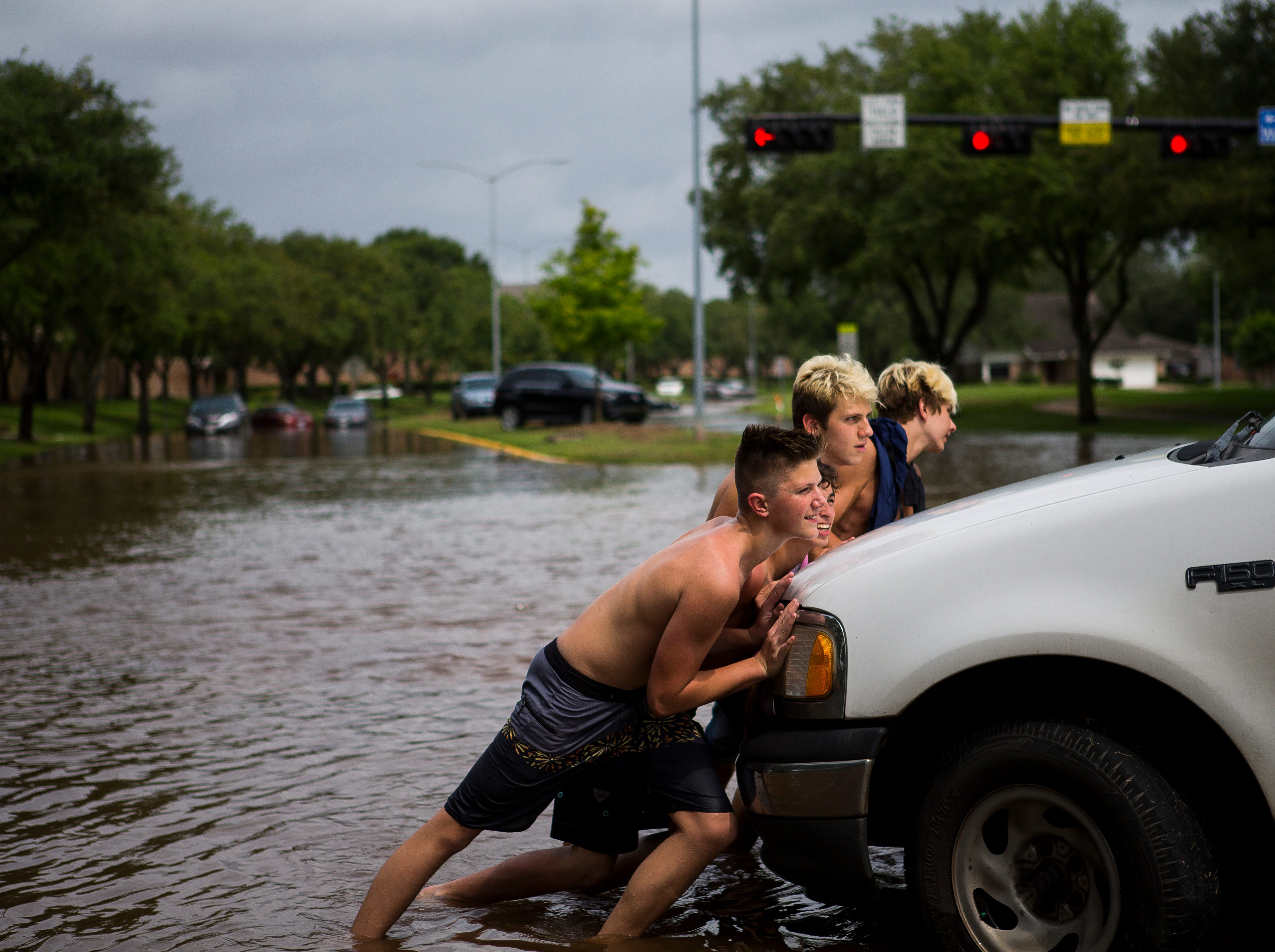 Teenagers help push a stuck truck off the flooded median at Sweetwater Boulevard and Austin Parkway in the Colony Bend neighborhood of Sugar Land, Texas on Wednesday, May 8, 2019. More rain is forecast for the coming days.