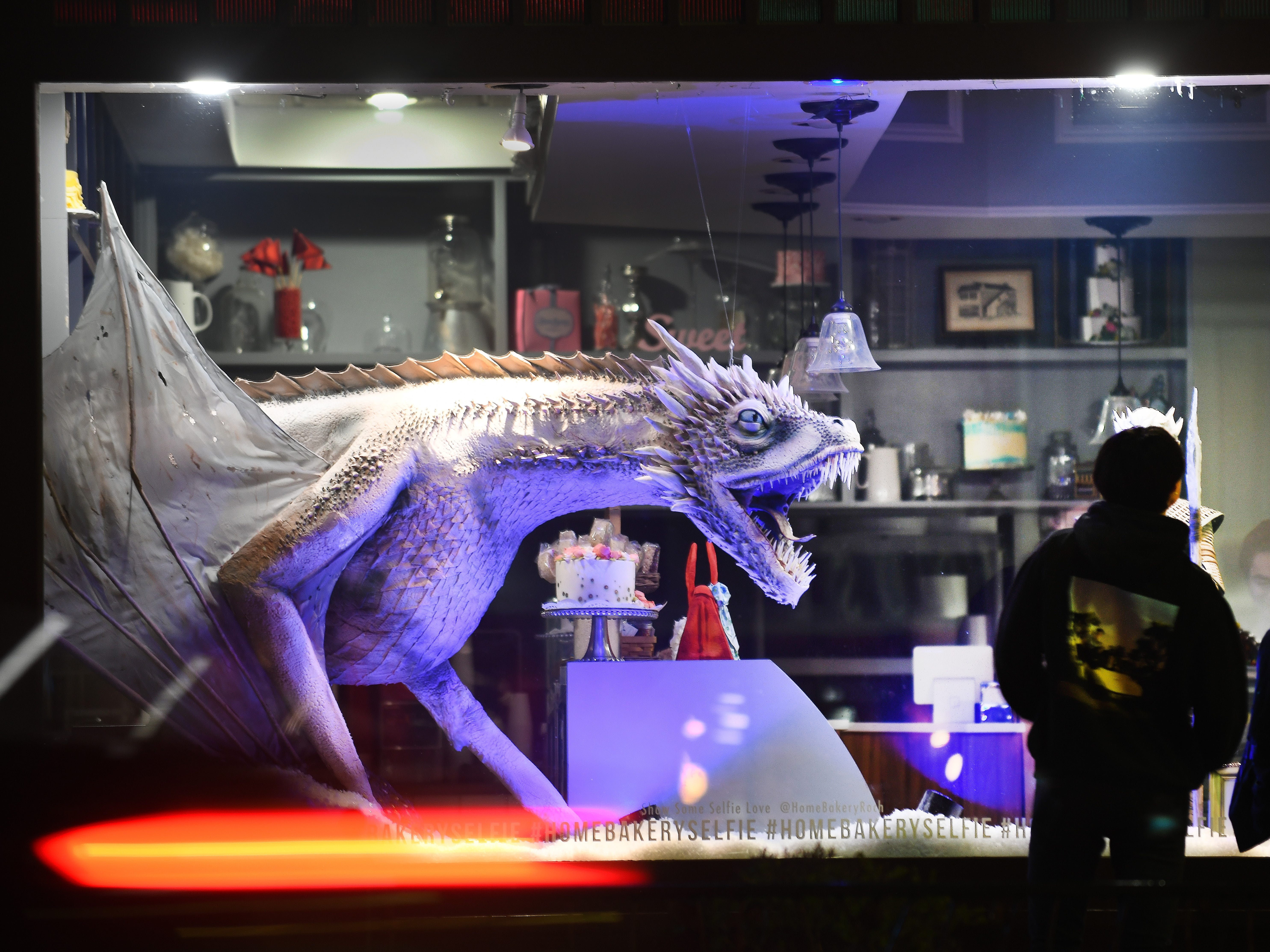 The ice dragon Viserion cake, measuring more than six feet long, intimidates   'Game of Thrones' fans, who are traveling from across Michigan to see the window display of The Home Bakery in Rochester.