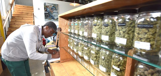 Utopia Gardens General Manager Donnell Cravens fills out state-required paperwork before making a medical-marijuana delivery, Wednesday afternoon.