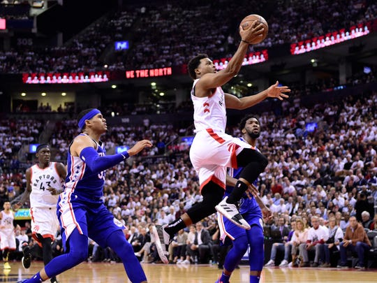 Raptors guard Kyle Lowry, right, scores against the 76ers during the second half of Game 5 on Tuesday.