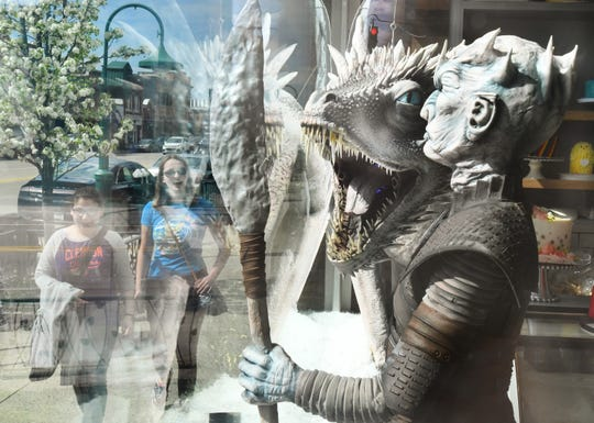 Lizzie Bouranis  and Dana Reeves walk by the 'Game of Thrones' inspired window complete with an ice dragon and the Night King at the Home Bakery in downtown Rochester.  It took more than 250 hours of labor by six decorators to create the  astounding confections.