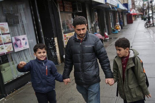 Sadek Ahmed walks with his sons Adel, 9, right, and Mutaz, 7, after picking them up from school in the Brooklyn borough of New York. Their mother, Amena Abdulkarem, is stuck in Yemen with her two younger sons, the boy's brothers.