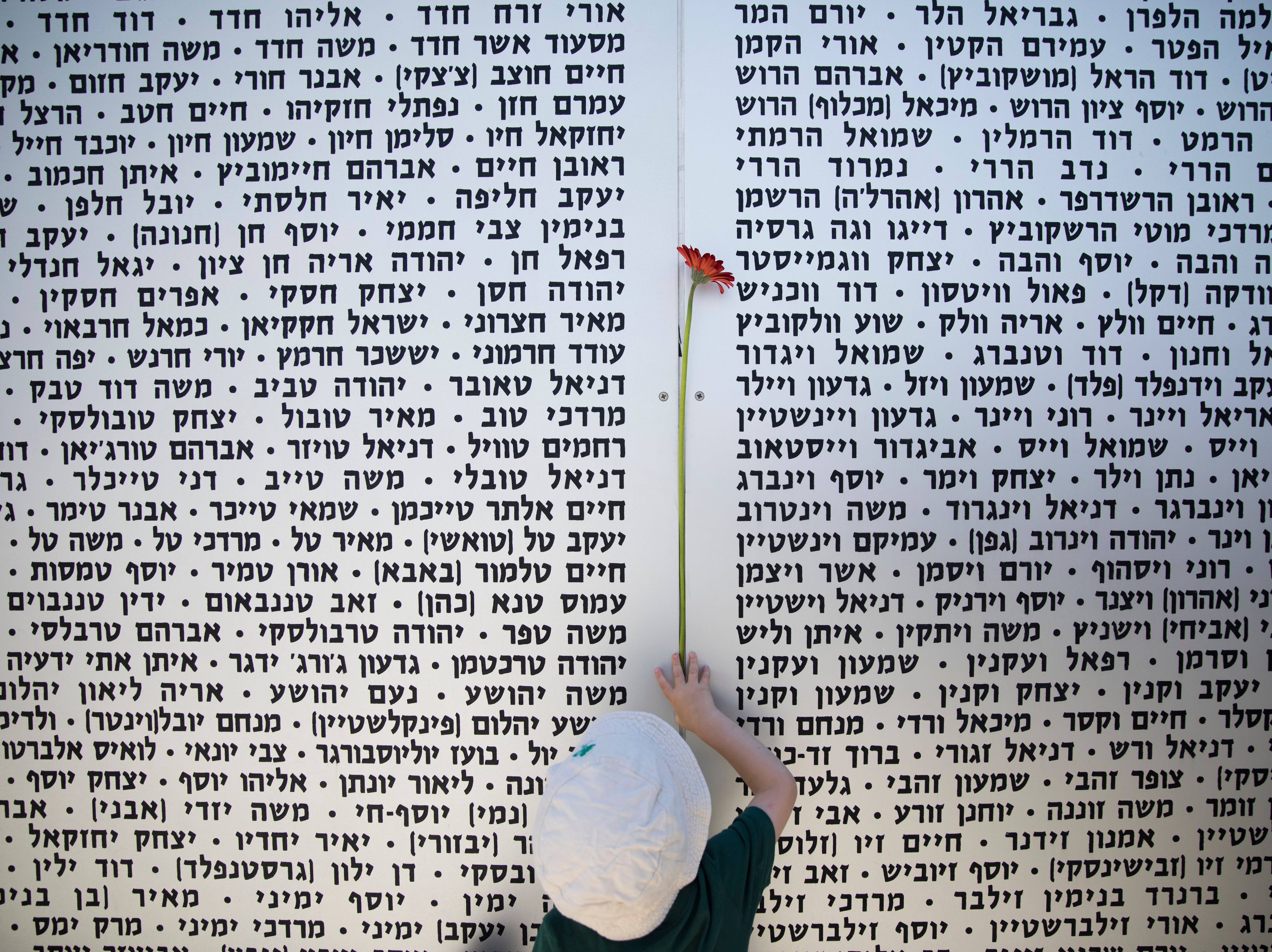 A boy hangs a rose on a wall of names following a ceremony marking the annual Memorial Day to remember fallen soldiers and victims of terror, at the Armored Corps memorial site Wednesday in Latrun, Israel.