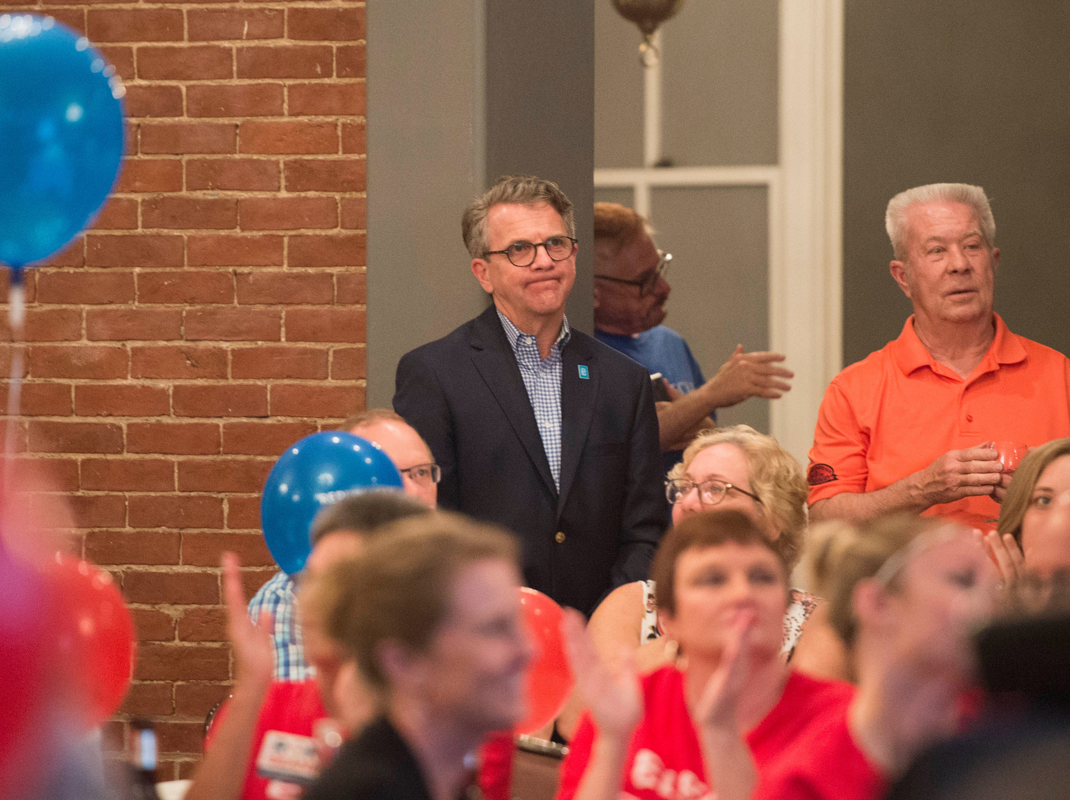 Evansville Mayor Lloyd Winnecke (R) reacts to pleasant remarks made by city council at-large candidate Zane Clodfelter (R) (not pictured) during before addressing the crowd after winning the primary election, Tuesday May 7, 2019.
