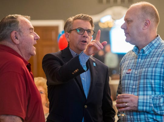 Evansville Mayor Lloyd Winnecke (R), middle, points to a projection while discussing the election with Wayne Parke, left, and David Clark, right, as they watch the municipal primary results to come in Tuesday, May 7, 2019.