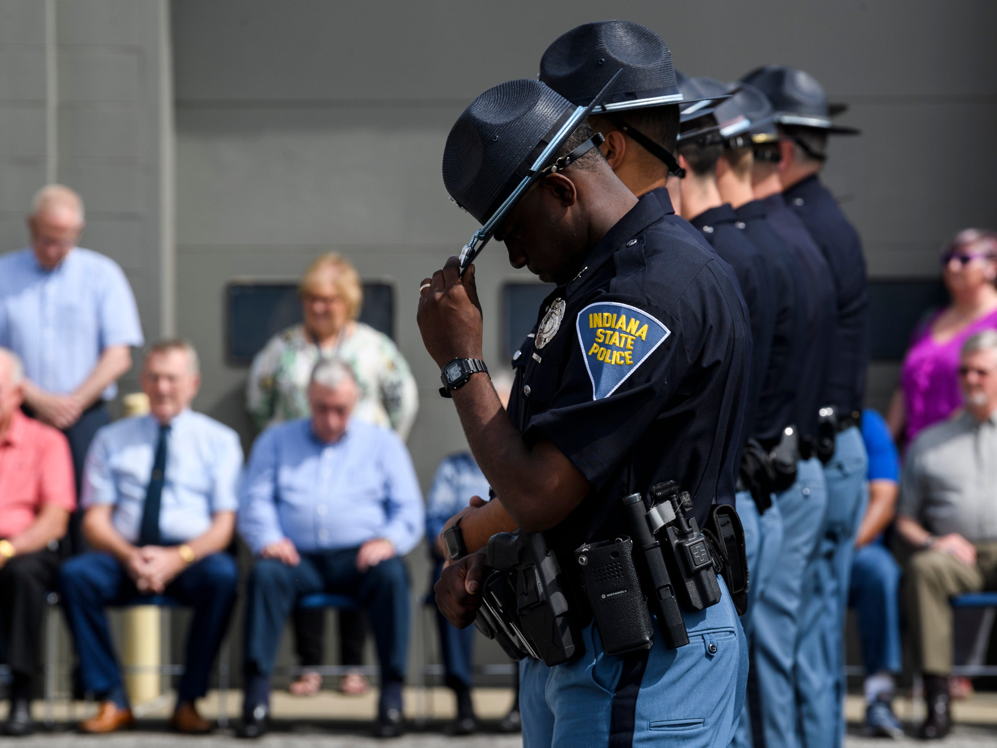 Trooper Trey Stewart, front center, tips his hat down as he listens to the names of 46 Indiana State Police officers who have died in the line of duty since 1933 during the annual ISP Memorial Service at the Evansville post, Wednesday morning, May 8, 2019.