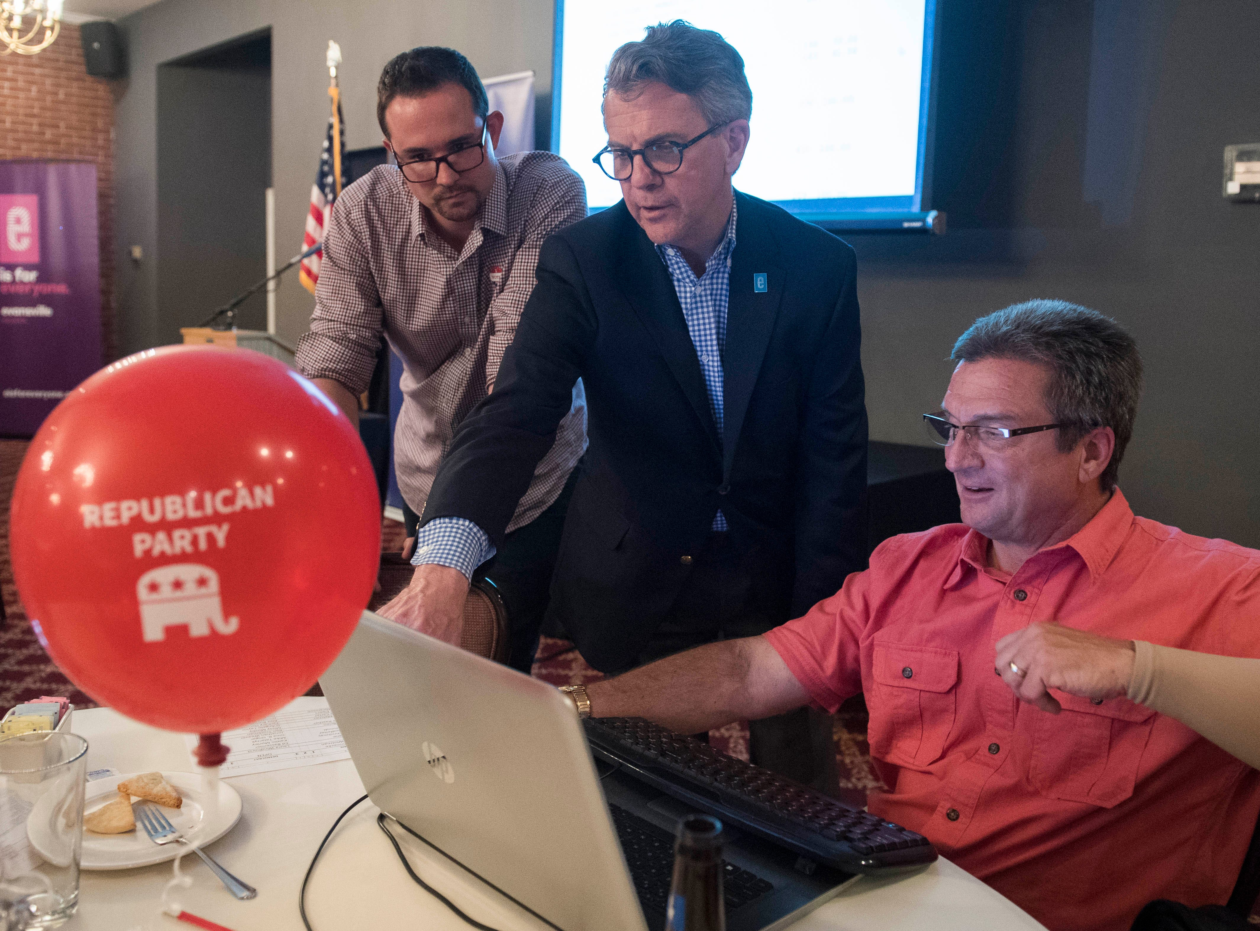 Zac Rascher, Mayor Lloyd Winnecke (R), middle, and Kevin  Harrison, right, look at primary election results as they come in Tuesday, May 7, 2019.