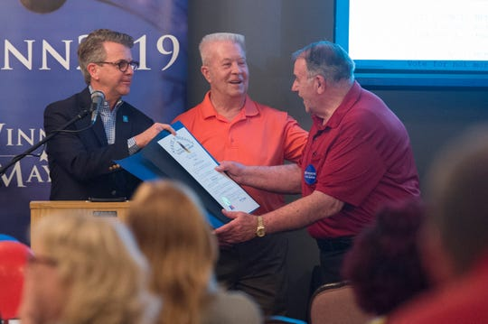 Evansville Mayor Lloyd Winnecke (R), left, presents Vanderburgh County Republican Party Chairman Wayne Parks, right, a Sagamore of the Wabash award Tuesday, May 7, 2019.