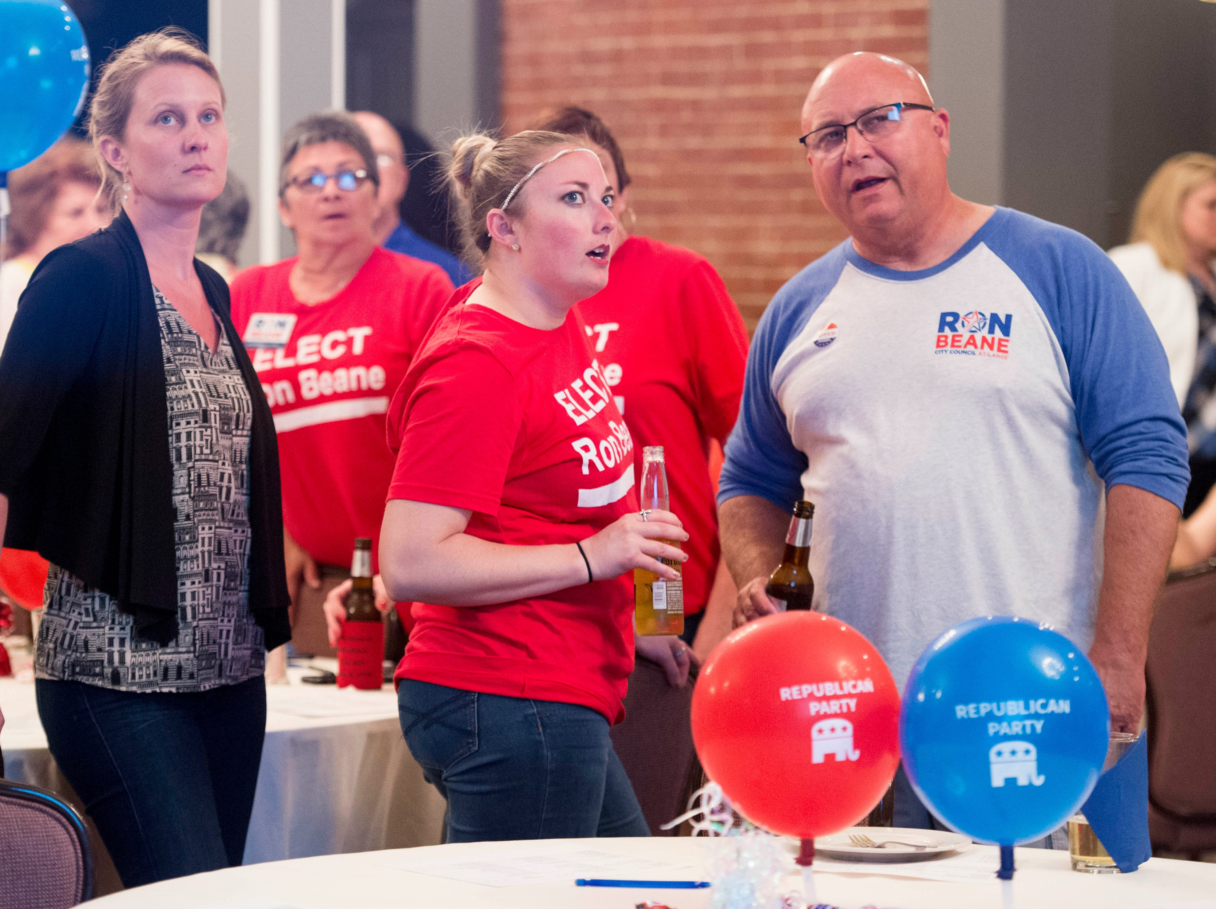 City council at-large candidate Ron Beane (R) supporters Shannon Begeman, left, Holly Dallmier, middle, and Allen Woodruff, right watch primary results update Tuesday, May 7, 2019.