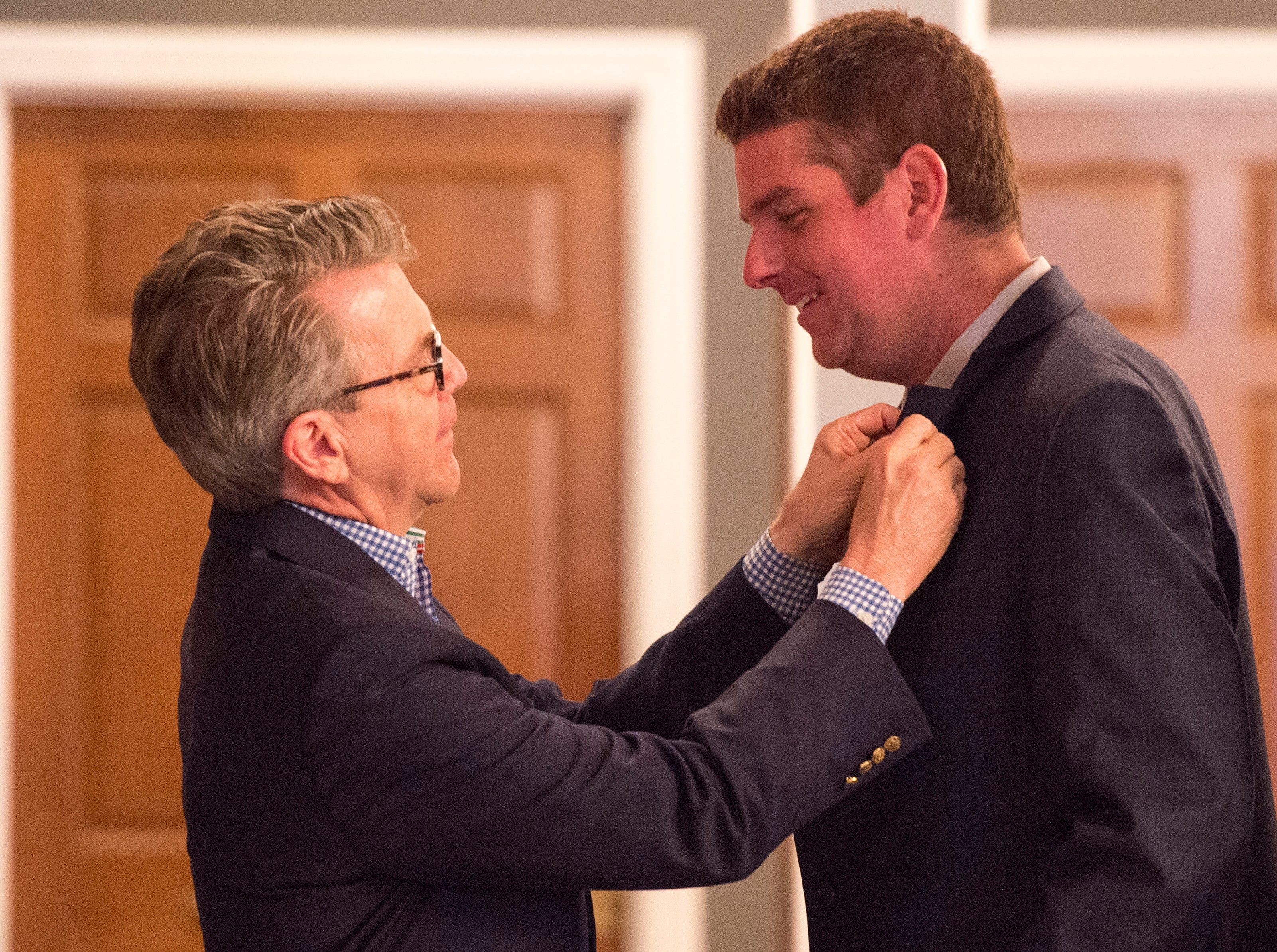 Evansville Mayor Lloyd Winnecke (R), left, adjust a lapel pin on city council at-large candidate Zane Clodfelter (R) during the Vanderburgh County Republican Party's watch party at Sauced! restaurant on Haynie's Corner Tuesday, May 7, 2019.