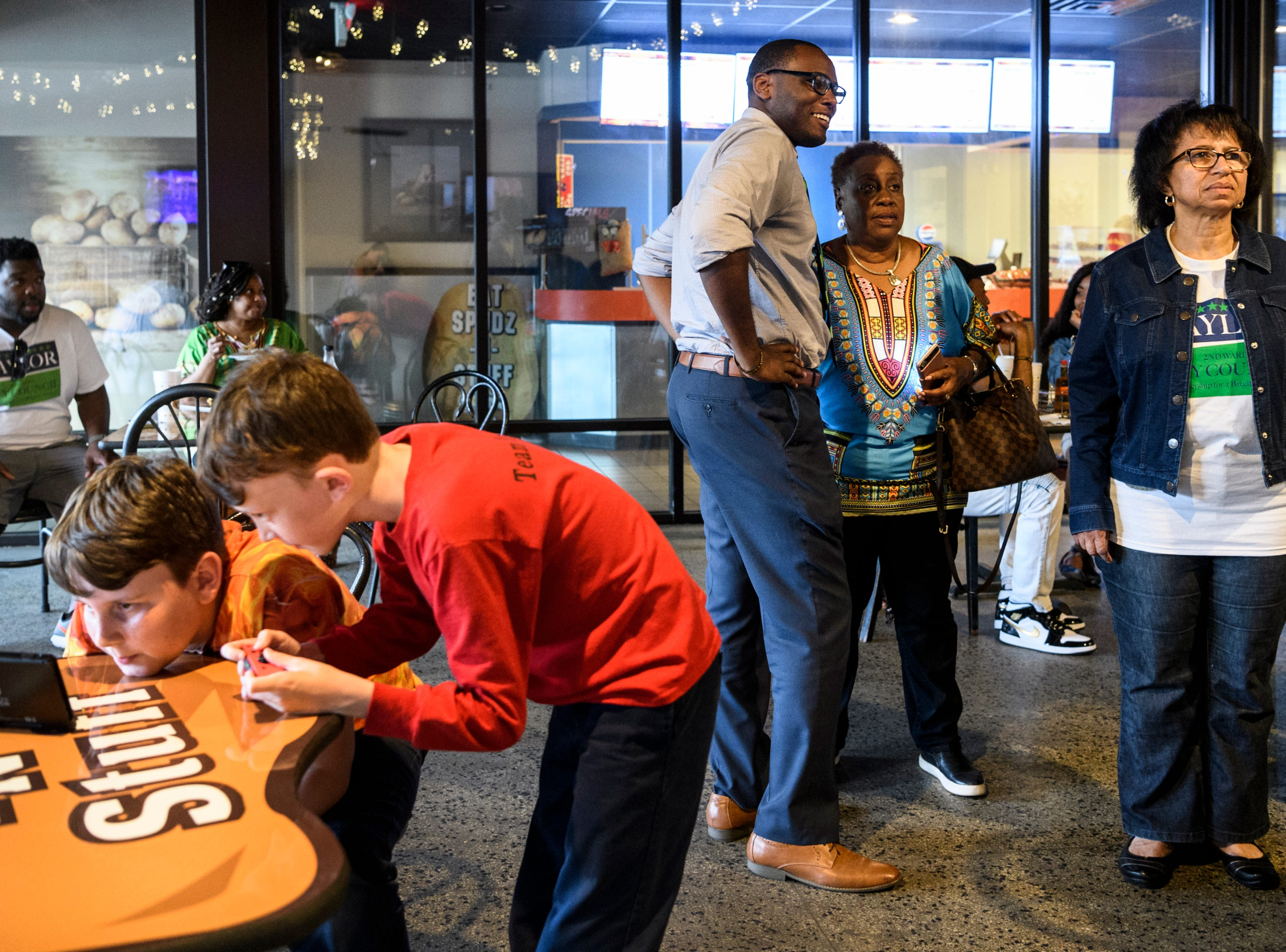 Sam, from left, and Peter Ungar, lay a game on their Nintendo Switch as D'Angelo Taylor, a second ward city council candidate, watches election results with Connie Robinson and others at Spudz-N-Stuff on Washington Avenue in Evansville, Ind., Tuesday, May 7, 2019. Gina Robinson Ungar, Sam and Peter's mother, won one of three democratic at-large spots while Taylor lost by 46 votes to 12-year incumbent Missy Mosby.