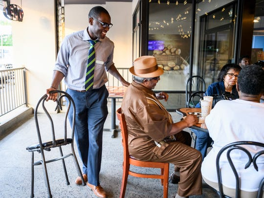 D'Angelo Taylor, left, greets supporters as he grabs a chair to sit in during a democratic primary election watch party at Spudz-N-Stuff on Washington Avenue in Evansville, Ind., Tuesday, May 7, 2019. He lost by 46 votes in a contentious second ward city council race to Missy Mosby (not pictured).
