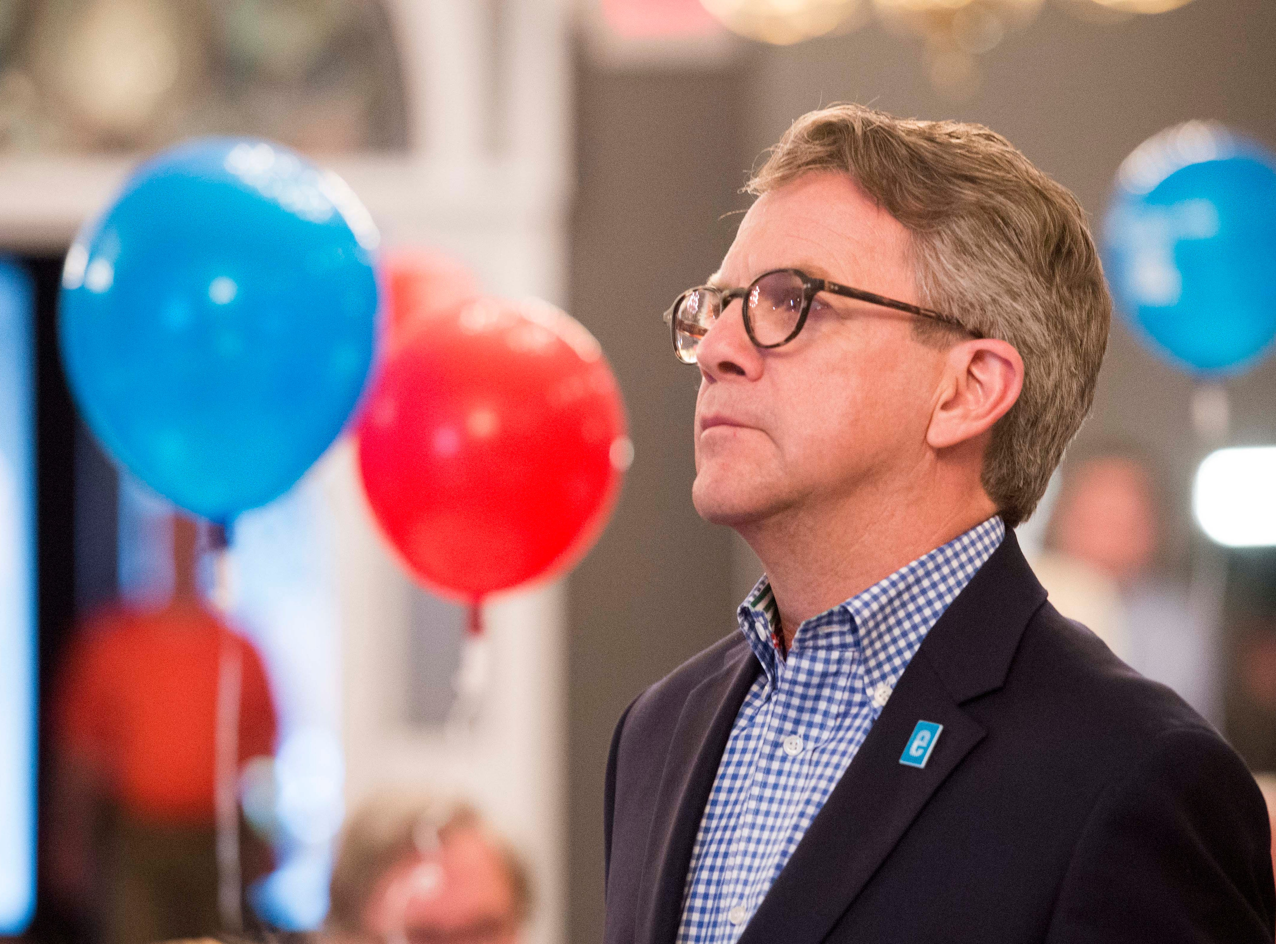 Evansville Mayor Lloyd Winnecke (R) stares a projection screen watching the municipal primary results to come in Tuesday, May 7, 2019.