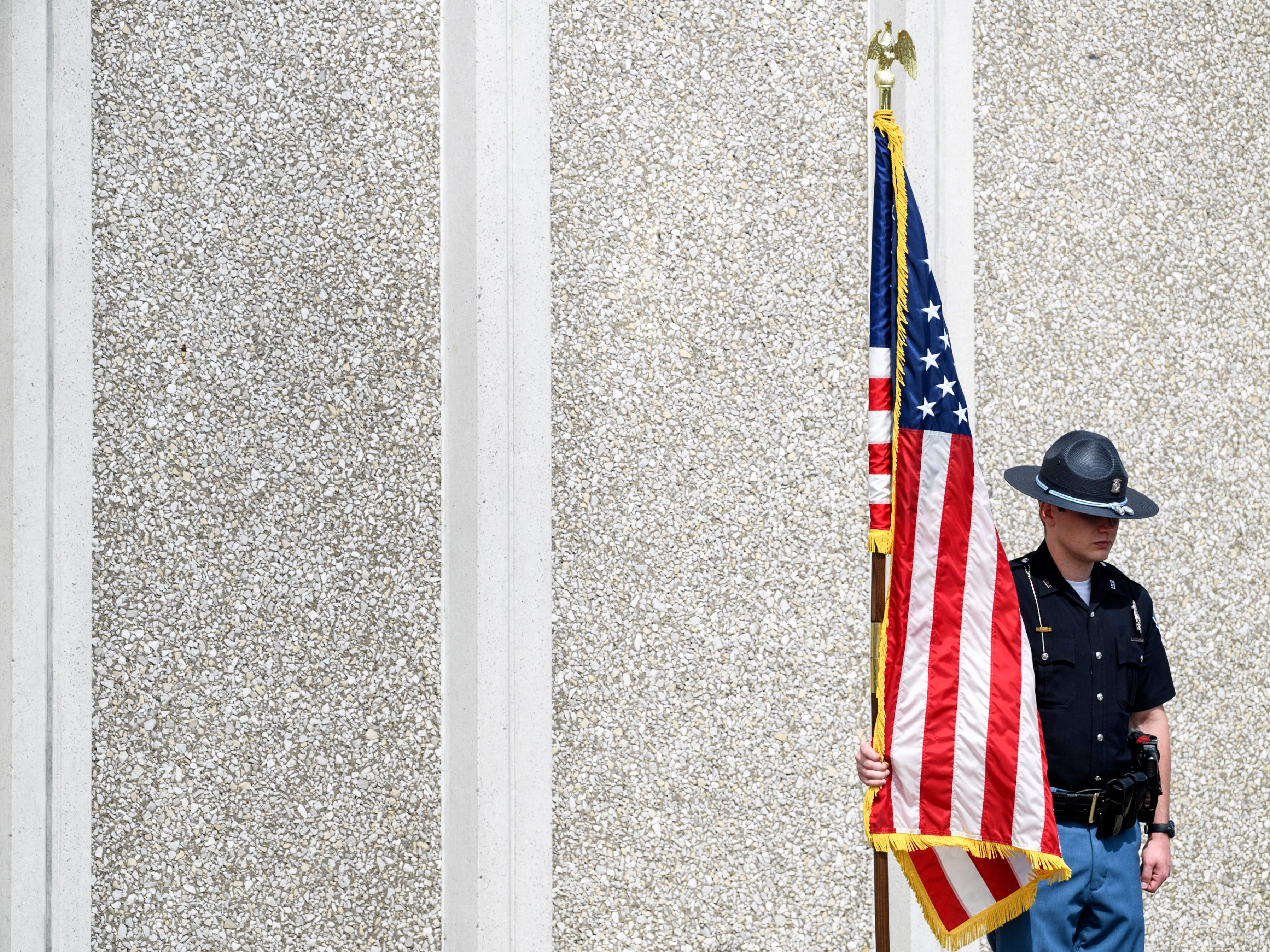 Trooper Daltyn Backes holds an American flag as all the names of Indiana State troopers who have died in the line of duty over the years are read aloud during the annual State Police Memorial Service held outside of the Police Post in Evansville, Ind., Wednesday morning, May 8, 2019. A total of 46 members of the ISP have died in the line of duty since the department's inception in 1933, with the most recent being Master Motor Carrier Inspector Robert E. Pitcher of Cambridge City, Ind., in September 2010.
