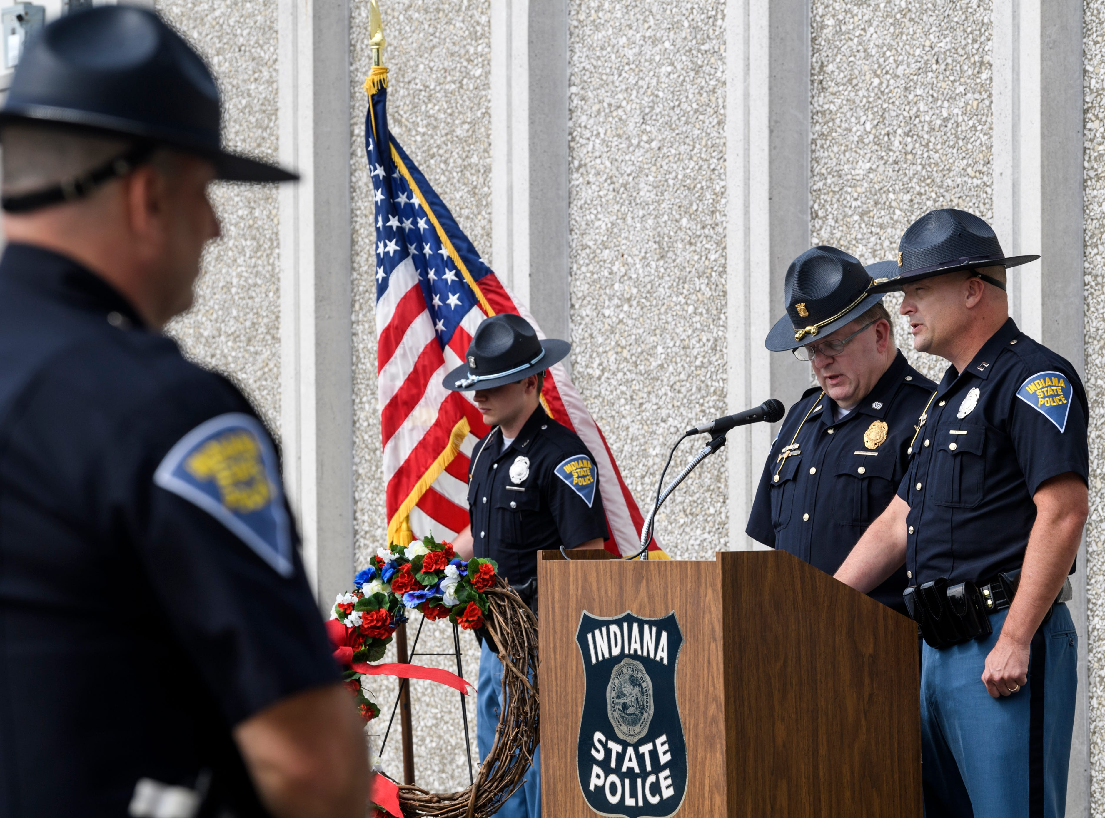 Indiana State Police troopers including Daltyn Backes, center left to right, listen as 1st Sgt, Tom Weber, Evansville's Assistant District Commander, and Capt. Robert Priest read the names of the 46 officers who have died in the line of duty since 1933 during an annual memorial service at ISP's Evansville post, Wednesday morning, May 8, 2019.